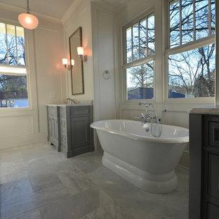 Klassisk inredning av ett mellanstort en-suite badrum, med luckor med profilerade fronter, grå skåp, ett fristående badkar, en toalettstol med hel cisternkåpa, vita väggar, marmorgolv, ett undermonterad handfat och marmorbänkskiva