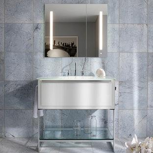 Exempel på ett maritimt badrum, med blå kakel, stenkakel, ett integrerad handfat och bänkskiva i glas