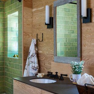 Modelo de cuarto de baño rústico, de tamaño medio, con combinación de ducha y bañera, baldosas y/o azulejos verdes, baldosas y/o azulejos de cerámica, ducha con cortina, armarios con paneles lisos, puertas de armario de madera oscura, lavabo bajoencimera, encimeras negras, bañera empotrada y paredes marrones