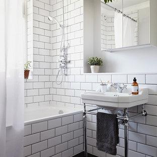 Klassisk inredning av ett badrum, med ett konsol handfat, vit kakel, tunnelbanekakel, vita väggar och mörkt trägolv