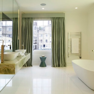 Design ideas for a large contemporary bathroom in London with a freestanding bath, mirror tiles, a vessel sink, white floors, white walls and green worktops.