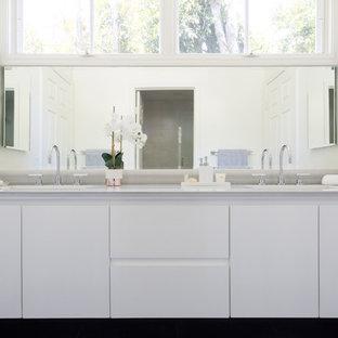 Modelo de cuarto de baño actual, de tamaño medio, con armarios con paneles lisos, puertas de armario blancas, baldosas y/o azulejos grises, baldosas y/o azulejos de piedra, paredes blancas, suelo de pizarra, lavabo bajoencimera, encimera de mármol, bañera encastrada y combinación de ducha y bañera