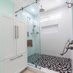 Источник вдохновения для домашнего уюта: большая ванная комната в современном стиле с фасадами в стиле шейкер, белыми фасадами, душем в нише, унитазом-моноблоком, белой плиткой, зелеными стенами, полом из ламината, душевой кабиной, врезной раковиной, столешницей из гранита, бежевым полом и душем с раздвижными дверями