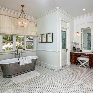 Ispirazione per una grande stanza da bagno padronale tradizionale con vasca freestanding, consolle stile comò, ante in legno bruno, pareti bianche, pavimento con piastrelle a mosaico, pavimento grigio e top grigio