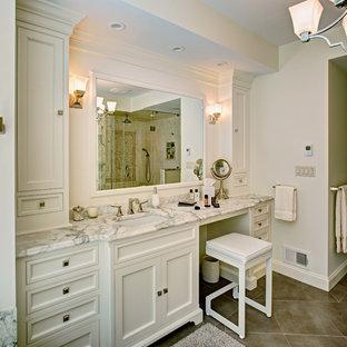 Bild på ett mellanstort vintage en-suite badrum, med luckor med profilerade fronter, vita skåp, en dusch i en alkov, beige kakel, vit kakel, marmorkakel, vita väggar, klinkergolv i porslin, ett undermonterad handfat, marmorbänkskiva, beiget golv och dusch med gångjärnsdörr