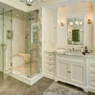Свежая идея для дизайна: главная ванная комната среднего размера в классическом стиле с фасадами с декоративным кантом, белыми фасадами, душем в нише, бежевой плиткой, белой плиткой, мраморной плиткой, белыми стенами, полом из керамогранита, врезной раковиной, мраморной столешницей, бежевым полом и душем с распашными дверями - отличное фото интерьера