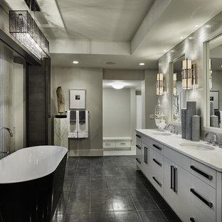 На фото: главная ванная комната среднего размера в стиле современная классика с врезной раковиной, плоскими фасадами, белыми фасадами, отдельно стоящей ванной, серой плиткой, плиткой из сланца, серыми стенами, бетонным полом, столешницей из искусственного кварца, серым полом и серой столешницей с