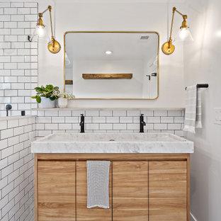 サンフランシスコのトランジショナルスタイルのおしゃれなバスルーム (浴槽なし) (フラットパネル扉のキャビネット、淡色木目調キャビネット、白いタイル、サブウェイタイル、白い壁、横長型シンク、洗面台2つ) の写真