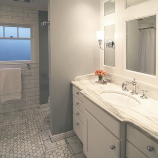 Elegant white tile and stone tile bathroom photo in Other with an undermount sink, furniture-like cabinets, white cabinets, marble countertops and a one-piece toilet