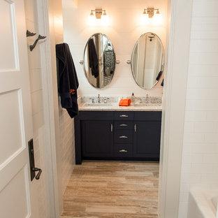 Inredning av ett klassiskt mellanstort badrum för barn, med möbel-liknande, blå skåp, ett badkar i en alkov, en dusch/badkar-kombination, flerfärgad kakel, tunnelbanekakel, vita väggar, klinkergolv i porslin, ett undermonterad handfat och bänkskiva i återvunnet glas