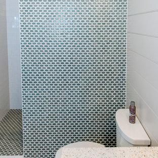 Imagen de cuarto de baño con ducha, actual, de tamaño medio, con armarios tipo mueble, puertas de armario blancas, ducha empotrada, sanitario de una pieza, baldosas y/o azulejos multicolor, baldosas y/o azulejos en mosaico, paredes blancas, suelo de baldosas de porcelana, lavabo bajoencimera y encimera de vidrio reciclado