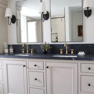 Foto de cuarto de baño principal, ecléctico, de tamaño medio, con armarios con rebordes decorativos, puertas de armario beige, baldosas y/o azulejos beige, encimera de esteatita y encimeras negras
