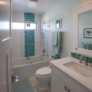 Alcove shower - small coastal kids' white tile and subway tile porcelain tile alcove shower idea in Los Angeles with an undermount sink, recessed-panel cabinets, white cabinets, solid surface countertops, a two-piece toilet and blue walls