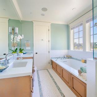 Aménagement d'une grand salle de bain principale bord de mer avec un lavabo encastré, une baignoire encastrée, une douche d'angle, un carrelage multicolore, carrelage en mosaïque, un mur bleu, un placard avec porte à panneau encastré, des portes de placard en bois clair, un sol en carrelage de terre cuite, un plan de toilette en surface solide, un sol blanc, une cabine de douche à porte battante et un plan de toilette blanc.