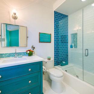 Idee per una stanza da bagno con doccia stile marinaro di medie dimensioni con lavabo da incasso, ante con riquadro incassato, ante blu, top in quarzo composito, vasca ad alcova, vasca/doccia, WC monopezzo, piastrelle blu, piastrelle a mosaico, pareti bianche, pavimento con piastrelle in ceramica, pavimento bianco, porta doccia a battente e top bianco