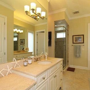 Esempio di una stanza da bagno padronale chic di medie dimensioni con lavabo sottopiano, ante bianche, top in granito, vasca giapponese, vasca/doccia, WC monopezzo, piastrelle beige, piastrelle in ceramica, pareti gialle e pavimento con piastrelle in ceramica