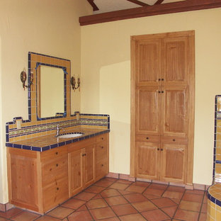Design ideas for a mediterranean ensuite bathroom in San Luis Obispo with a submerged sink, shaker cabinets, light wood cabinets, a corner bath, yellow tiles, ceramic tiles, yellow walls and terracotta flooring.