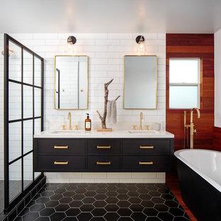 Идея дизайна: главная ванная комната среднего размера в современном стиле с плоскими фасадами, черными фасадами, отдельно стоящей ванной, открытым душем, белой плиткой, керамогранитной плиткой, белыми стенами, полом из цементной плитки, врезной раковиной, столешницей из искусственного кварца, черным полом, открытым душем и белой столешницей