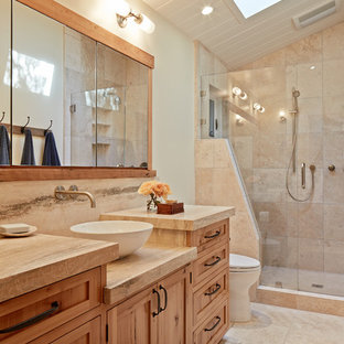 Diseño de cuarto de baño rural con lavabo sobreencimera, armarios estilo shaker, puertas de armario de madera oscura, ducha empotrada, baldosas y/o azulejos beige, paredes beige y baldosas y/o azulejos de travertino