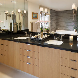 Design ideas for a mediterranean bathroom in Santa Barbara with a submerged sink, flat-panel cabinets, light wood cabinets and grey tiles.