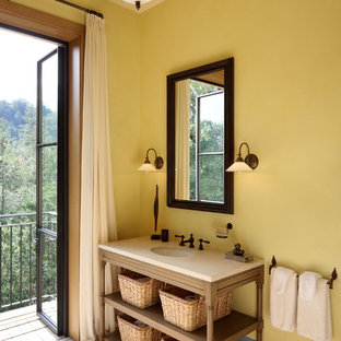 Photo of a mediterranean bathroom in Other with furniture-like cabinets, yellow walls and brown floor.