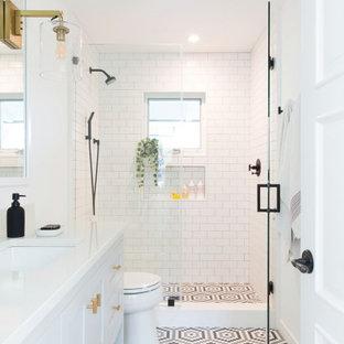 Inspiration för mellanstora klassiska vitt badrum för barn, med skåp i shakerstil, vita skåp, en dusch i en alkov, vit kakel, tunnelbanekakel, vita väggar, mosaikgolv, ett undermonterad handfat, flerfärgat golv och dusch med gångjärnsdörr