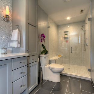 Klassisches Badezimmer mit Schrankfronten im Shaker-Stil, grauen Schränken, Duschnische, Wandtoilette mit Spülkasten, weißen Fliesen, grauer Wandfarbe und schwarzem Boden in Chicago