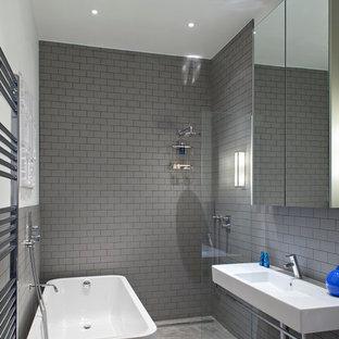 Diseño de cuarto de baño contemporáneo con lavabo suspendido, bañera exenta, baldosas y/o azulejos grises, baldosas y/o azulejos de cemento, paredes grises y ducha a ras de suelo