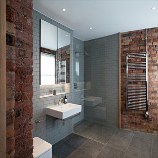 Example of a trendy gray tile and subway tile corner shower design in London with a wall-mount sink and gray walls