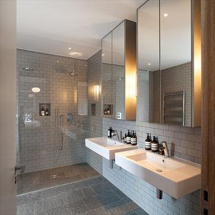 Immagine di una stanza da bagno minimal di medie dimensioni con lavabo sospeso, doccia ad angolo, piastrelle grigie, piastrelle diamantate e pareti grigie