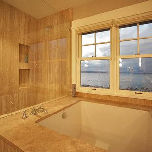 シアトルの中くらいのラスティックスタイルのおしゃれなマスターバスルーム (アンダーマウント型浴槽、オープン型シャワー、ベージュのタイル、磁器タイル、ベージュの壁、ライムストーンの床、ライムストーンの洗面台、ベージュの床、オープンシャワー、ベージュのカウンター) の写真