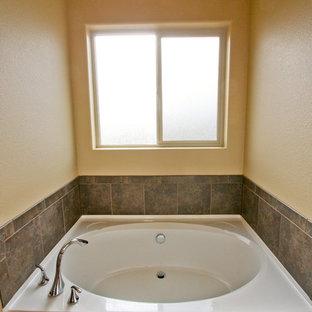 Foto de cuarto de baño principal con lavabo encastrado, armarios estilo shaker, puertas de armario de madera oscura, encimera de laminado, bañera encastrada, ducha empotrada, baldosas y/o azulejos marrones, baldosas y/o azulejos de piedra, paredes amarillas y suelo de linóleo