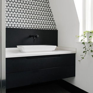 This is an example of a small modern family bathroom in London with flat-panel cabinets, black cabinets, a corner shower, a one-piece toilet, multi-coloured tiles, ceramic tiles, white walls, vinyl flooring, a console sink, solid surface worktops, black floors and a hinged door.