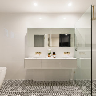 Design ideas for a contemporary bathroom in Brisbane with flat-panel cabinets, white cabinets, a freestanding tub, a curbless shower, white tile, an integrated sink, multi-coloured floor, an open shower and white benchtops.