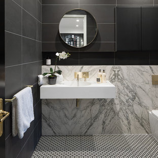 Photo of a contemporary 3/4 bathroom in Brisbane with a corner shower, a one-piece toilet, black tile, gray tile, a wall-mount sink, multi-coloured floor, a hinged shower door and white benchtops.