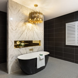 Design ideas for a contemporary bathroom in Brisbane with black cabinets, a freestanding tub, black tile, an integrated sink and multi-coloured floor.