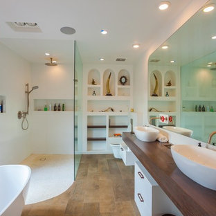 Inspiration for a mid-sized contemporary master white tile and porcelain tile medium tone wood floor and brown floor bathroom remodel in Los Angeles with white cabinets, a wall-mount toilet, white walls, a vessel sink, wood countertops, open cabinets and brown countertops