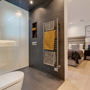 Contemporary ensuite bathroom in London with a wall mounted toilet, a built-in shower, grey tiles, grey walls, grey floors and an open shower.