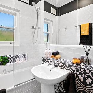 Kleines Modernes Badezimmer En Suite mit Glasfronten, weißen Schränken, Einbaubadewanne, Duschbadewanne, Wandtoilette, weißen Fliesen, Keramikfliesen, schwarzer Wandfarbe, Keramikboden, Sockelwaschbecken, gefliestem Waschtisch, schwarzem Boden und schwarzer Waschtischplatte in Sydney