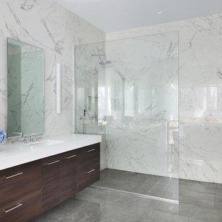 На фото: со средним бюджетом главные ванные комнаты среднего размера в стиле модернизм с плоскими фасадами, темными деревянными фасадами, отдельно стоящей ванной, душем без бортиков, раздельным унитазом, белой плиткой, керамогранитной плиткой, белыми стенами, полом из керамогранита, врезной раковиной, столешницей из искусственного кварца, серым полом, открытым душем и белой столешницей