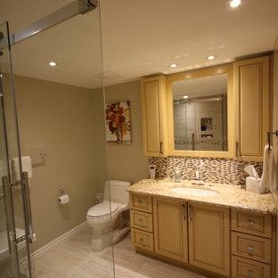 Esempio di una stanza da bagno padronale tradizionale di medie dimensioni con ante con bugna sagomata, ante gialle, doccia ad angolo, WC monopezzo, piastrelle multicolore, piastrelle di vetro, pareti beige, pavimento con piastrelle in ceramica, lavabo sottopiano, top in granito, pavimento beige, porta doccia scorrevole e top beige