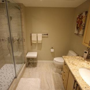 Immagine di una stanza da bagno padronale chic di medie dimensioni con ante con bugna sagomata, ante gialle, doccia ad angolo, WC monopezzo, piastrelle multicolore, piastrelle di vetro, pareti beige, pavimento con piastrelle in ceramica, lavabo sottopiano, top in granito, pavimento beige, porta doccia scorrevole e top beige