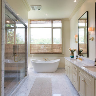 Example of a transitional master marble tile and white tile marble floor and white floor bathroom design in New Orleans with beaded inset cabinets, beige cabinets, beige walls, an undermount sink, marble countertops and a hinged shower door