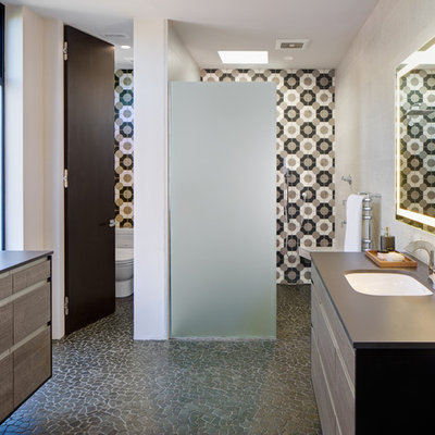Inspiration for a mid-sized modern master beige tile, black tile, white tile and porcelain tile pebble tile floor and gray floor bathroom remodel in San Diego with flat-panel cabinets, distressed cabinets, a one-piece toilet, white walls, an undermount sink and solid surface countertops
