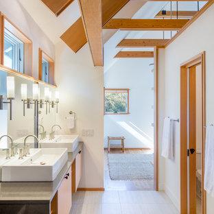 Inredning av ett modernt en-suite badrum, med släta luckor, orange skåp, vita väggar och ett fristående handfat