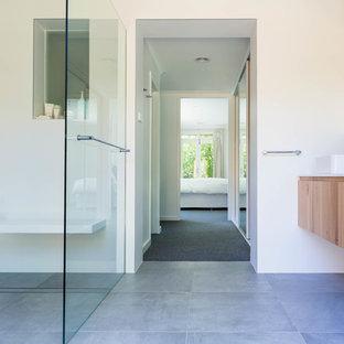 На фото: со средним бюджетом главные ванные комнаты среднего размера в современном стиле с фасадами островного типа, светлыми деревянными фасадами, открытым душем, унитазом-моноблоком, синей плиткой, плиткой мозаикой, белыми стенами, полом из керамической плитки, настольной раковиной, столешницей из ламината, серым полом и душем с распашными дверями