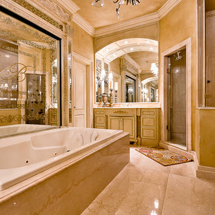 Example of a classic master marble floor drop-in bathtub design in Little Rock