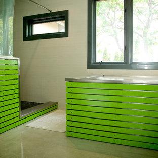 Esempio di una grande stanza da bagno padronale minimal con ante verdi, vasca da incasso, doccia ad angolo, piastrelle beige, piastrelle in gres porcellanato, pareti verdi, pavimento in cemento, lavabo sottopiano, top in acciaio inossidabile, pavimento grigio e doccia con tenda