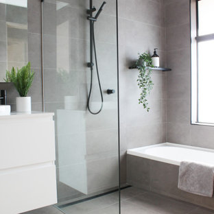 This is an example of a mid-sized modern kids wet room bathroom in Perth with flat-panel cabinets, white cabinets, gray tile, porcelain tile, porcelain floors, a vessel sink, engineered quartz benchtops, grey floor, an open shower, white benchtops, a single vanity, a floating vanity and an alcove tub.