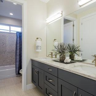 Immagine di una stanza da bagno con doccia contemporanea di medie dimensioni con ante in stile shaker, ante grigie, vasca ad alcova, vasca/doccia, pareti beige, pavimento in linoleum, lavabo rettangolare e top in granito